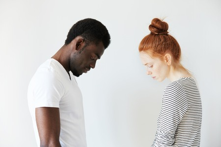 sorrowful: Sad couple looking down with their heads bowed in front of each other. Side view portrait of two sorrowful people: young Caucasian redhead girl and Afro-American melancholic man. Negative emotions.