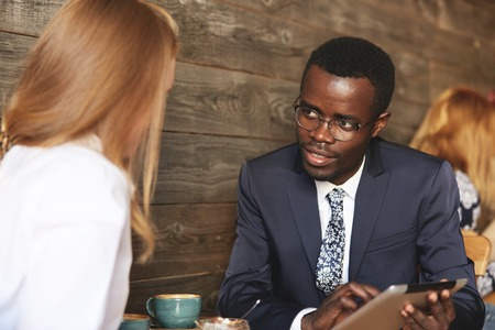 two women and one man: Two business associates of different races having a meeting at a cafe: young African man in formal suit and glasses showing a presentation to his redhead Caucasian female colleague on digital tablet Stock Photo