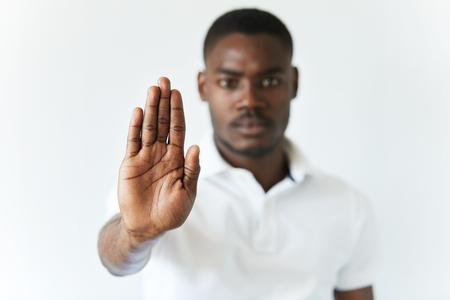 falta de respeto: Retrato de seus mano masculina que sostiene afroamericano en la señal de stop, advertencia y le impide algo malo, mirando a la cámara con expresión preocupada. Selectivo se centran en la palma