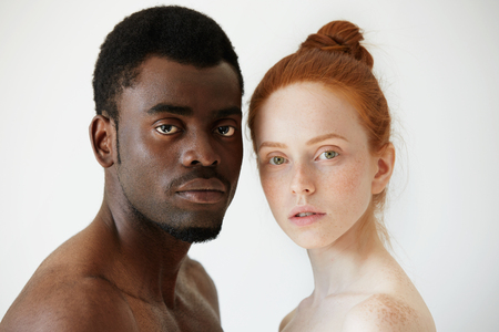 race relations: Black and white. Headshot of African man and Caucasian woman standing shirtless and looking at the camera with serious expression. Portrait of young beautiful interracial couple. Mixed race relations Stock Photo