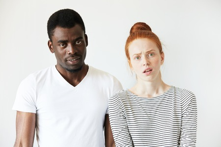 breaking up: African man wearing white T-shirt standing next to his Caucasian girlfriend in sailor shirt, looking at the camera with disgusted and annoyed expression, quarrelling or breaking up. Human relations