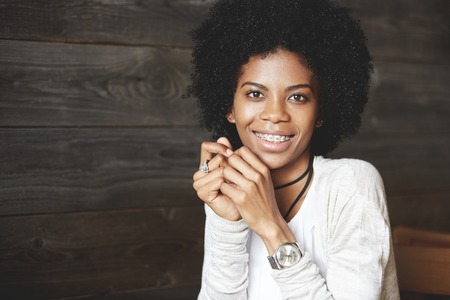 Close up shot ofattractive happy cheerful dark-skinned young woman looking and smiling at the camera, showing white teeth with braces, holding hands at her face. Human face expressions and emotions Stock Photo