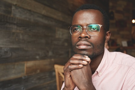 Attractive young black writer in pink shirt, sitting at a cafe with dreaming face expression, looking through the window, gaining inspiration in urban landscape outside, reflected on his oval glasses Stockfoto