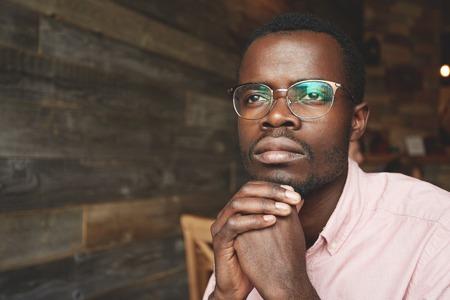 Aantrekkelijke jonge zwarte schrijver in roze shirt, zittend in een cafe met dromen gezicht expressie, kijkend door het raam, het verkrijgen van inspiratie in stedelijk landschap buiten, weerspiegeld op zijn ovale bril Stockfoto - 60514670