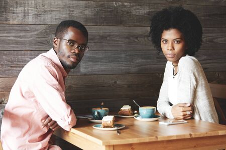american dessert: Handsome African American student in shirt and glasses sitting at a cafe with his dark-skinned female group mate in casual clothes, looking at the camera, having dessert after classes at university