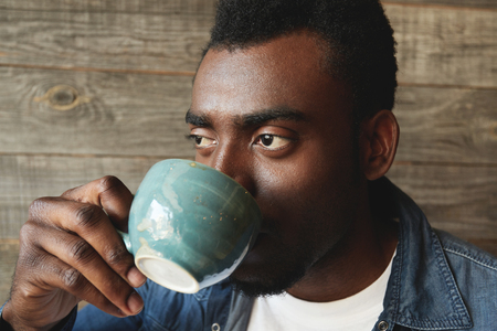 enyoing: Close up portrait of African-American person drinking a cup of tasty coffee in the morning. Young man is looking away plunged deep into his thoughts, making big plans for upcoming day and future.
