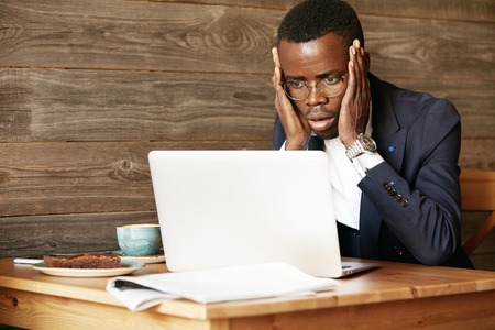 distant work: Handsome AFrican corporate worker in glasses using laptop for distant work, sitting at the hotel lobby, looking at the camera in shock, surprised with sensational news, holding hands on his cheeks