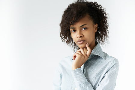 Young African female in striped shirt looking at the camera with serious pensive expression, touching her cheek with a finger, posing against white studio wall with copy space for your information