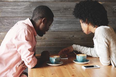 Liefde en relaties. Mooie jonge Afro-Amerikaanse echtpaar met een datum in een cafe, drinken cappuccino's, het bekijken van foto's op de mobiele telefoon tijdens de vergadering op de houten tafel. Terug te bekijken