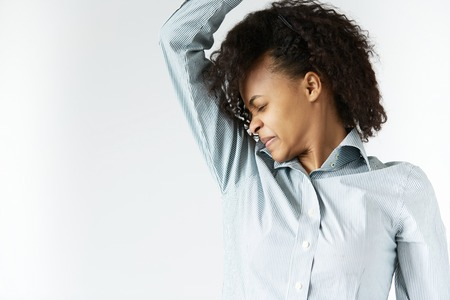 hyperhidrosis: Bad smelling concept. Profile portrait of African woman in striped shirt with black Afro hairstyle, sniffing her armpit with disgusted expression, grimacing, closing her eyes, cant stand stink.