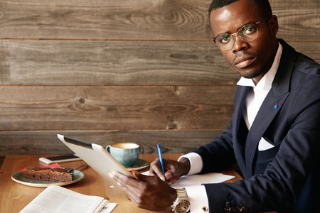 distant work: Handsome successful African entrepreneur wearing formal suit and spectacles, signing papers while using tablet. Portrait of dark-skinned man holding digital device for distant work at a coffee shop Stock Photo