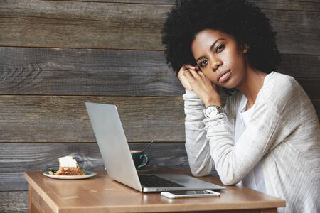 leaning on elbows: People and lifestyle concept. Beautiful African woman with Afro haircut wearing stylish clothes, looking at the camera with serious expression, leaning her elbows on the table with laptop and phone
