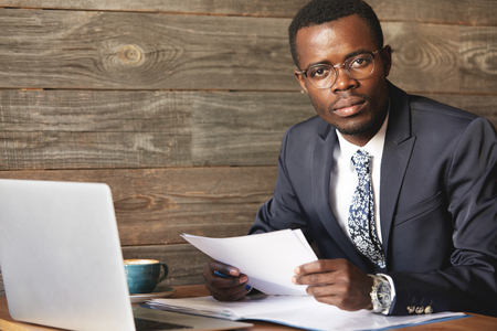 look pleased: Successful top-manager sitting, working with papers and computer in comfortable caf?. Elegant official suit, wristwatches and happy look of African businessman say he is pleased with productive job.