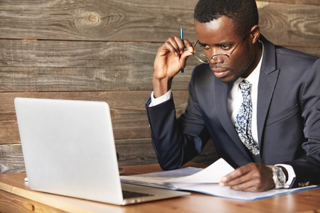 Serious African American businessman looking over his glasses on laptop screen. Focused gentlemen checking papers with information in his computer, sitting at coworking place with free connection.