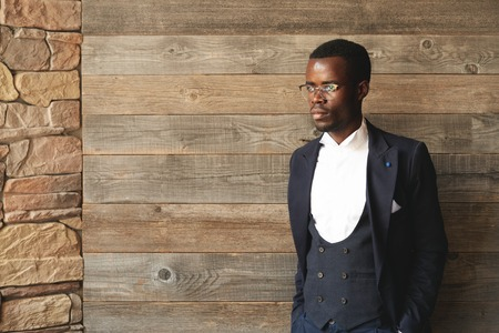 decent: Graceful African American gentleman standing indoors in daylight on wooden background and looking away. Decent, elegant man in round glasses is dressed in official suit with vest and snow white shirt.