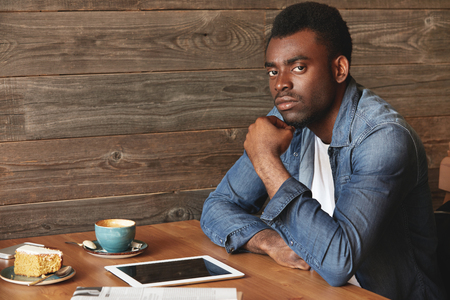 american dessert: Serious African American man in denim shirt sitting in a caf?. He has coffee, dessert, digital tablet and newspaper on wooden table. His thoughtful posture makes him look plunged into problem-solving.
