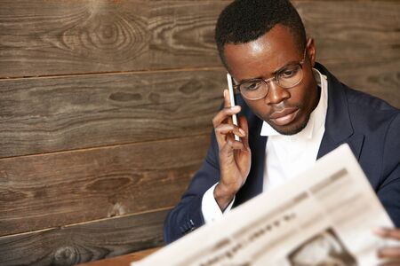 prestigious: Confident Kenyan student of prestigious University, looking busy and concentrated in oval-shaped glasses, making a call interested in a newspaper advertisement, sitting against wooden wall background