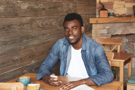 Beautiful portrait of African man sitting in caf? with free wireless connection, drinking fresh coffee with dessert. Satisfied youngster is comfy with morning breakfast and beginning of a new day.