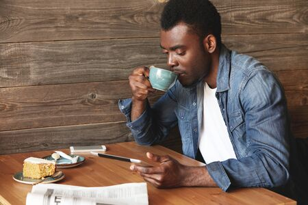 comfy: Attractive African American guy reading book on his tablet and drinking tasty coffee with honey dessert in comfy restaurant. He looks down on his device, focused on book or articles in internet. Stock Photo