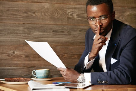 Top secret. Serious African businessman in formal suit holding a finger at his lips, saying shh, asking to keep silent while reading confidential papers, looking at the camera against wooden wall