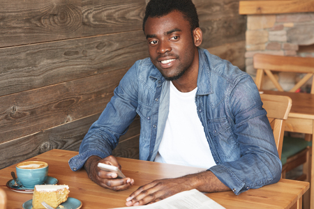 lunchtime: Young African gentleman in casual clothes holding smartphone and sitting in comfy caf?. Happy man pensively looking away and resting hands on table with coffee. Positive mood, weekend, lunch-time. Stock Photo