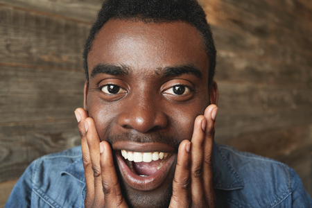mouth opened: Happy and amazed African American male looking exuberantly at camera with hands on cheeks and mouth opened. Attractive man in denim short on brown background agreeably surprised by good news. Stock Photo