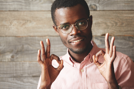 allright: Close up portrait of handsome young man looking and smiling at the camera, gesturing OK sign with both hands, showing that everything is great. Positive human emotions and facial expressions