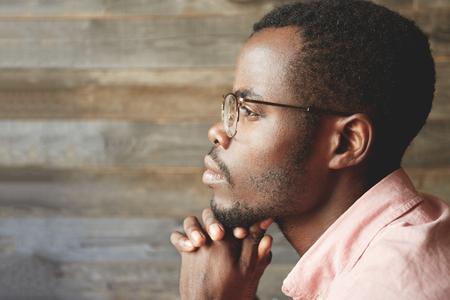 プロファイルの木製の背景に分離された彼の交差させた手にあごを持つ、美しさを考えて距離を調べてグラス、毛、健康的な顔で若い黒人男性のヘ