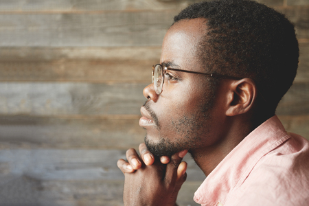 Profile headshot of young black man in glasses, with hairy, healthy face, looking into the distance, contemplating the beauty, with his chin on his crossed hands, isolated on a wooden background