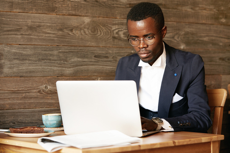distant work: Business and success. Handsome successful African American man wearing formal suit, oval glasses and watches, using laptop computer for distant work, looking at the screen with serious face expression