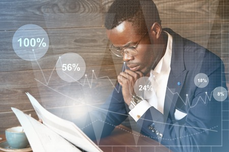 financier: Interest rates, percentage ratio interface. Successful dark-skinned financier in glasses looking through papers with serious and concentrated look while sitting against wooden wall background LANG_EVOIMAGES