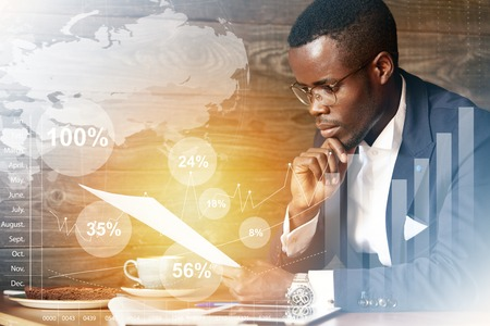 financier: Film effect. Worldwide connection interface. African financier dressed in elegant suit sitting at a cafe, holding papers, reading documents with concentrated attentive expression, touching his chin