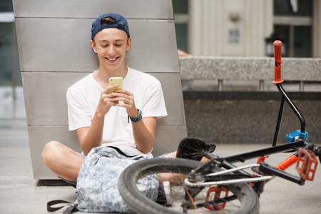 People, technology and communication concept. Handsome Caucasian 15-year old bike rider in street wear using wireless internet connection for communicating via social networks while relaxing outdoor
