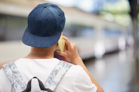 Back view of high school student boy carrying backpack going to school. Caucasian teenager in snapback making phone call while waiting his friends on the platform at the railway station. Film effect Banco de Imagens