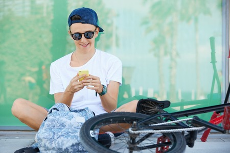 Smiling 15-year old schoolboy in street wear and stylish shades messaging via social networks with happy look, relaxing in the shadow on sunny day during his ride on BMX bike in the city center