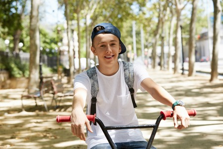 urban people: Urban biking - handsome Caucasian teenage boy wearing white T-shirt and snapback riding his BMX bicycle in the city park, looking and smiling at the camera. People, lifestyle and leisure concept LANG_EVOIMAGES