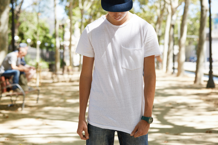 Portrait of teenage 15-year old boy wearing cap over his eyes, pulling down his white blank T-shirt with copy space for your promotional content, looking down, standing against city park background