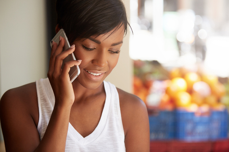 People and technology concept. Young African female student with short black haircut making phone calls, talking to her friend, discussing plans for summer vacations with happy and cheerful expression