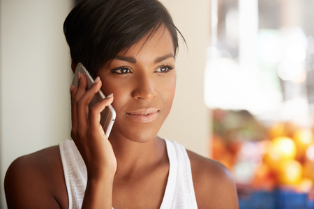 Headshot of sad dark-skinned student girl talking on mobile phone to her mother, disappointed because of failed exam at university, listening attentively, looking into distance with serious expression