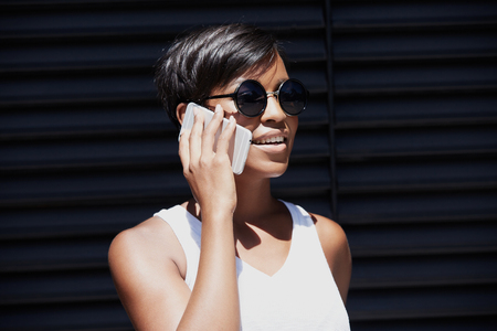 Attractive successful African female in round hipster sunglasses looking into distance with cheerful expression, having a business talk with her partner on mobile phone. Technology and communication