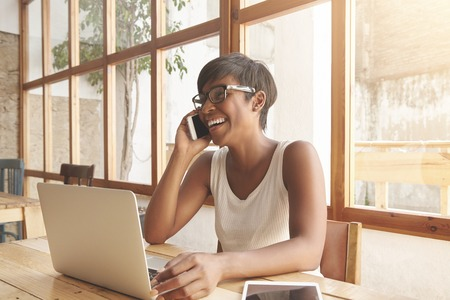 remembering: Portrait of young charismatic African adult woman laughing while talking on cellphone with her man, remembering good old days and their first date, black woman sitting at cafeteria using laptop