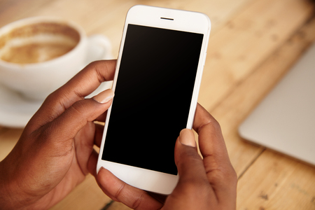 downloading content: Close up of black womans hands holding smart phone with blank copy space for your advertising content or promotional information. Female downloading updates on her mobile phone, sitting at a cafe LANG_EVOIMAGES