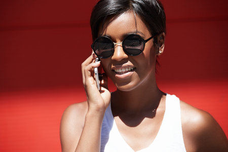Successful dark-skinned female choreographer talking on cell phone with dance studio owner about new workshop, walking down the street, passing by red wall with copy space for your promotional content Stock Photo