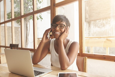 olive skin: Attractive young woman discussing her business projects on phone. Smiling brunette with olive skin and short haircut is sitting in cosy caf� with laptop and working with digital devices at hand.