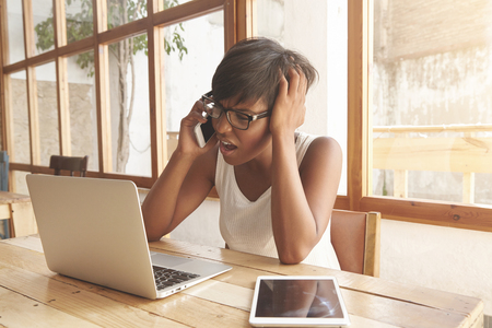 sleeveless top: Upset female freelancer talking on phone indoors near the window. Dark-skinned girl in white sleeveless top frowning her eyebrows and touching her head with disappointed look. Negative emotions. LANG_EVOIMAGES