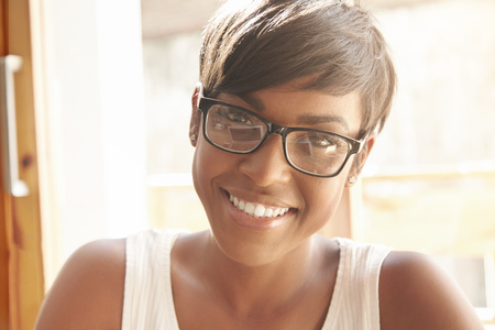 spanish looking: Nice close-up portrait of young girl in geeky glasses with pixie cut. Intelligent Spanish woman with shinny smile and brown eyes happily looking at camera. Successful lifestyle concept and happiness. LANG_EVOIMAGES
