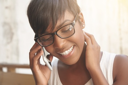 Smiling brown-skinned girl talking on phone. Lovely Spanish woman with stylish short haircut and shinny earrings looks great in her geeky glasses and white summer top. Positive emotions and talks concept.