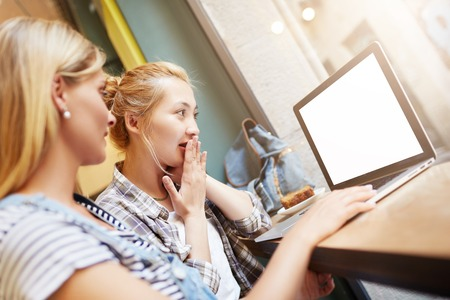 Positive and warm picture of two girls surfing net with wireless connection on up-to-date laptop. Youngsters dressed in casual clothes hanging out in caf�. Surprise facial expression, weekend mood.