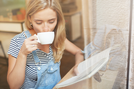 Pretty young woman sipping coffee and reading magazine near the window. Nice and warm shot of Caucasian girl in casual clothes through the window glass. Positive and calm atmosphere of harmony.