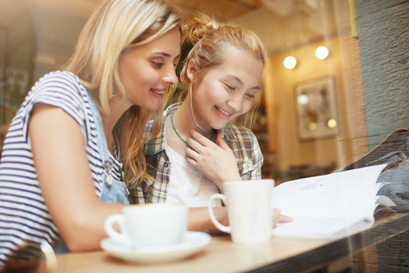Two young blond girls reading fashion magazine in comfy coffee shop near the window. Nice woman with long hair smiling and the other girl with bun in checked shirt looking at page with pleasure. LANG_EVOIMAGES